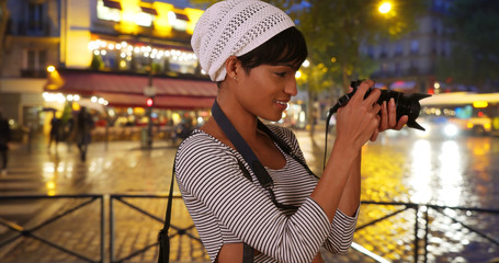 Creative young black woman photographing urban nightlife on digital camera