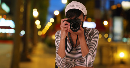 Hip female African photographer taking pictures in Paris France