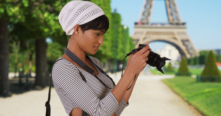 Pretty African-American woman taking photos near Eiffel Tower Paris France
