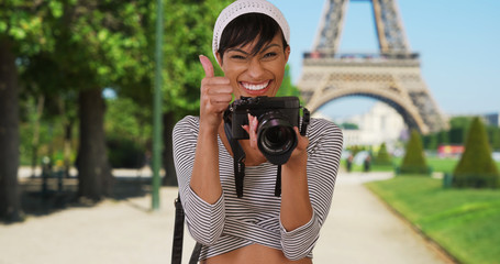 Pretty African-American woman turns and takes photo of viewer near Eiffel Tower