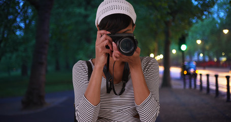 Ethnic millennial female taking photograph at public park at night