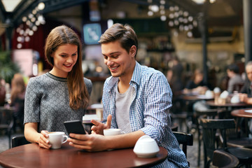 Couple Drinking Coffee On Date In Cafe