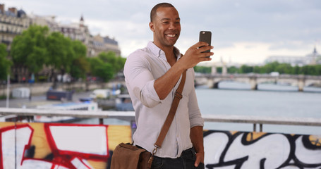 Modern Black man traveling in Paris France using smartphone outside