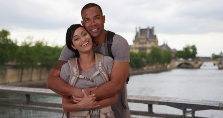 African-American couple in Paris pose lovingly near Seine River