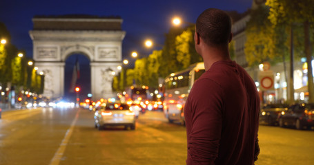African man on vacation in Paris taking look around city near Arc de Triomphe