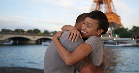 Tender African couple embracing by Seine River near Eiffel Tower