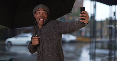 African-American man with umbrella taking selfies on smartphone in the rain