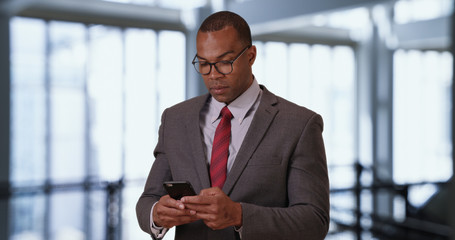 Accomplished male black CEO checking messages on phone inside office building