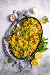 Classic valencian paella from rice with seafood and green pea - traditional dish of spanish cuisine.Top view.