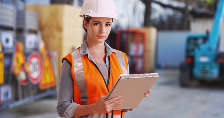 Young white lady on construction site checking things off on clipboard