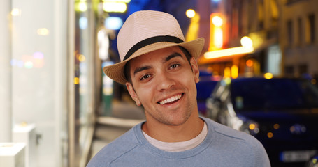 Attractive happy Latino male smiling on city street ready for the club