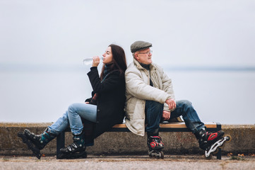 A girl on rollers drinks water from a bottle. Father and daughter on roller skates sit on a bench. Sport and water. Active old people in retirement.