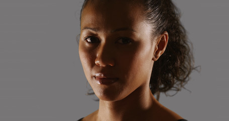 Mixed race woman athlete looking at camera on grey background