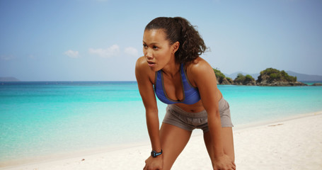 Toned Filipino woman jogging on the beach resting hands on knees