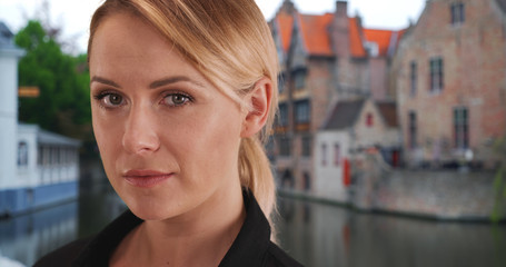 Close-up portrait of gorgeous white woman looking intently at camera in Bruges
