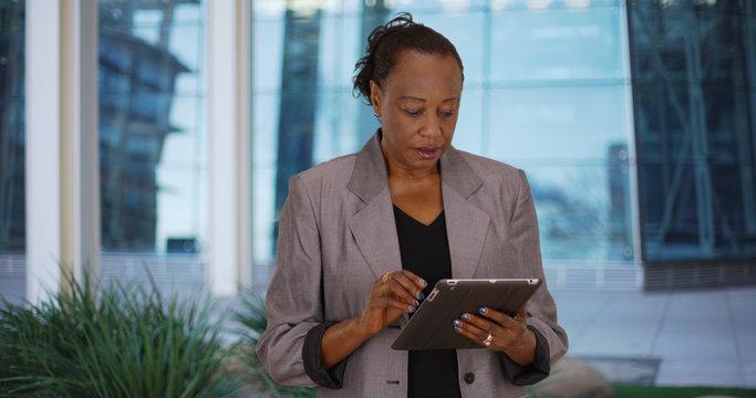 Older black businesswoman uses digital tablet outside office building
