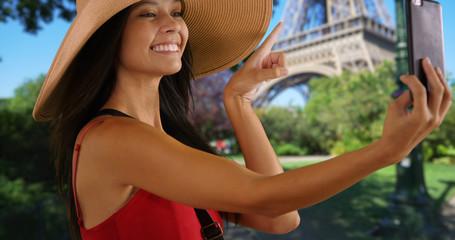 Close up of happy millennial girl taking a selfie in Paris near Eiffel Tower
