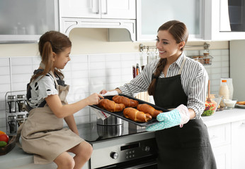 Young nanny with cute little girl cooking together in kitchen