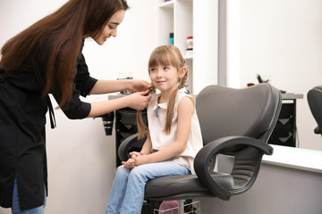 Professional female hairdresser working with little girl in salon