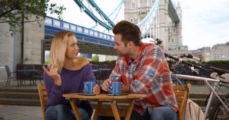 Couple chatting and drinking coffee by the Tower Bridge