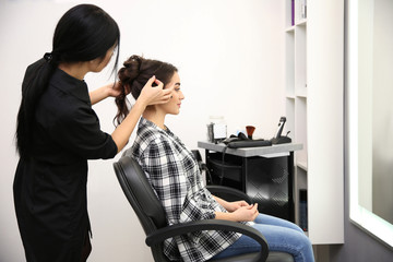 Professional female hairdresser working with client in salon