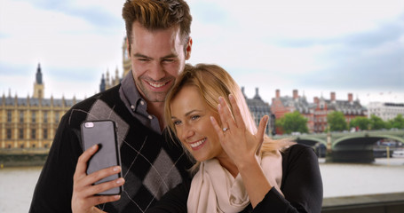 Newly engaged couple take a selfie in London to share the news with friends