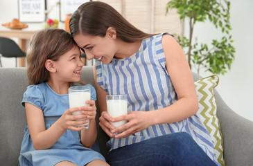 Mother and daughter with glasses of milk in living room