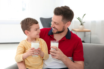 Father and son with glasses of milk in living room