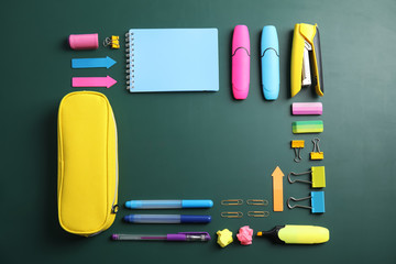 Flat lay composition with different school stationery on chalkboard surface