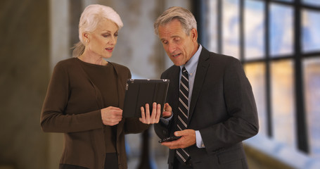 Male and female executives using digital tablet in the office