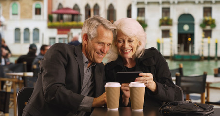 Portrait of Caucasian male and female using mobile device on their vacation