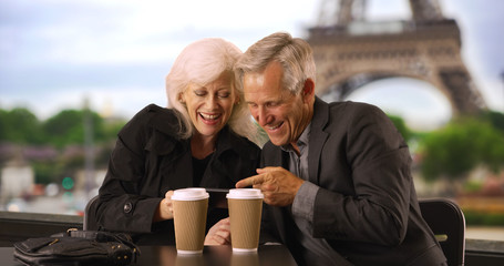 Mature couple looking at smartphone pictures in Paris