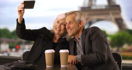 Happy mature couple taking a selfie in Paris