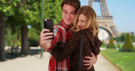 Loving young couple take fun selfies in front of the Eiffel Tower
