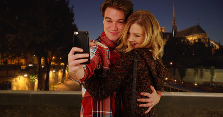 Happy young couple taking fun selfies in Paris at night