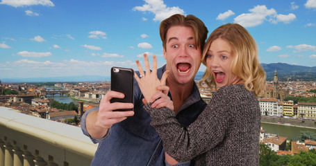 Newly engaged couple taking a selfie in Florence smiling and laughing