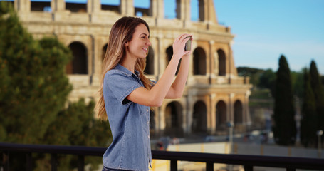 Smiling woman tourist taking picture on vacation in Rome