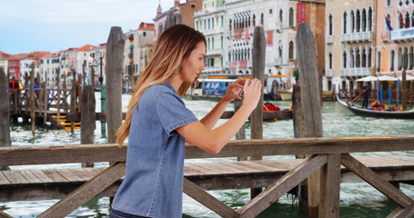 Woman tourist taking picture of gondolas in Venice to share with friends