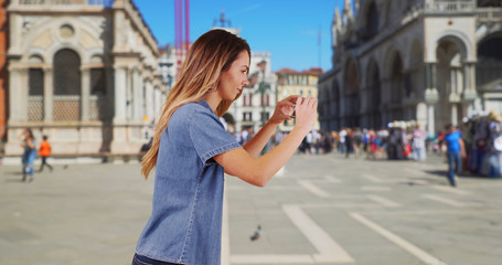 Happy woman tourist taking picture in San Marco Piazza with smartphone
