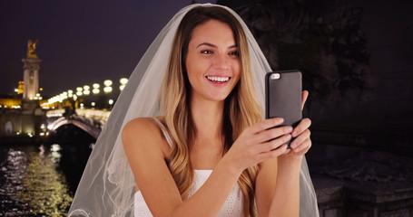 Joyful bride taking fun selfies in Paris at night