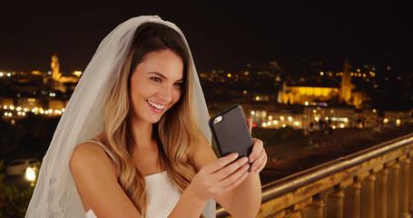 Joyful bride taking fun selfies in Florence on beautiful night