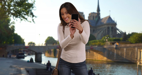 Cute Latin woman in Paris taking picture of friend as seen from friends pov
