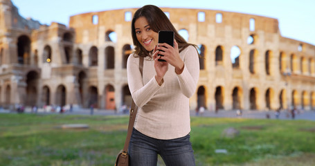 Cute Latin woman in Rome taking picture of friend as seen from friends pov