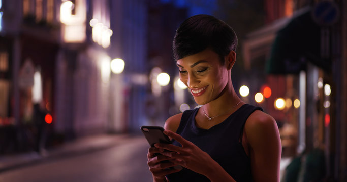 Pretty smiling African American female reads text message on the street at night