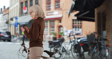 Active senior Caucasian woman with bicycle texting on phone on sidewalk