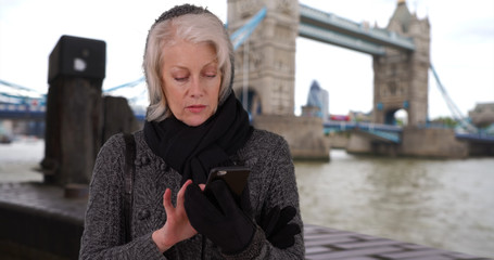 Older woman tourist in London using mobile phone next to River Thames