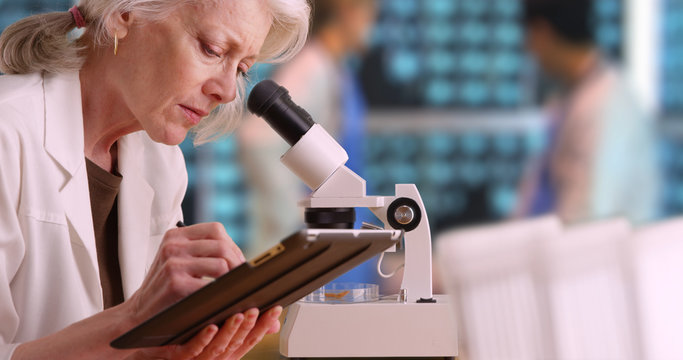 Senior woman medical researcher taking notes on tablet computer in busy lab