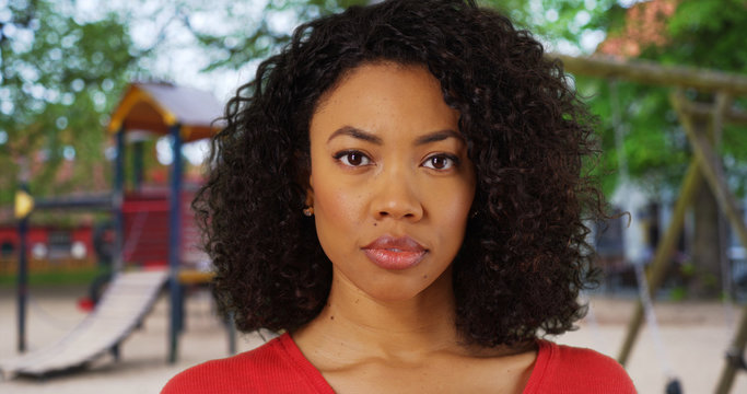 African-American woman with serious look on face at playground in public park