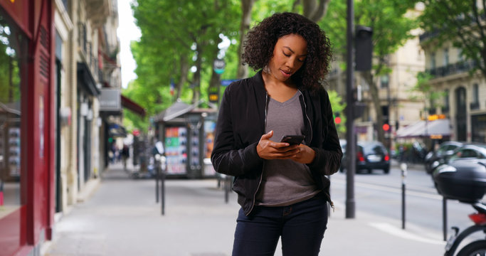 Pretty black woman standing on urban street using cellphone
