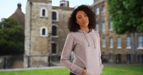 Black millennial woman on vacation in England wearing a grey hoodie